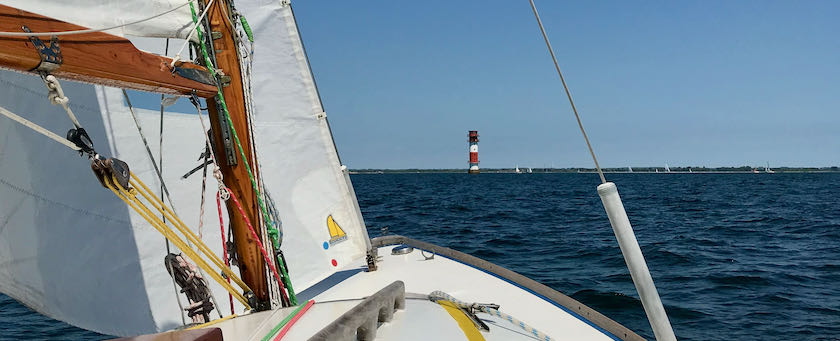 View from a sailing ship across the water spotting a lighthouse