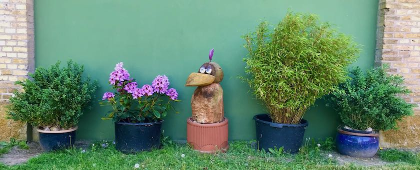 Row of potted plants with a wooden bird sculpture in the middle